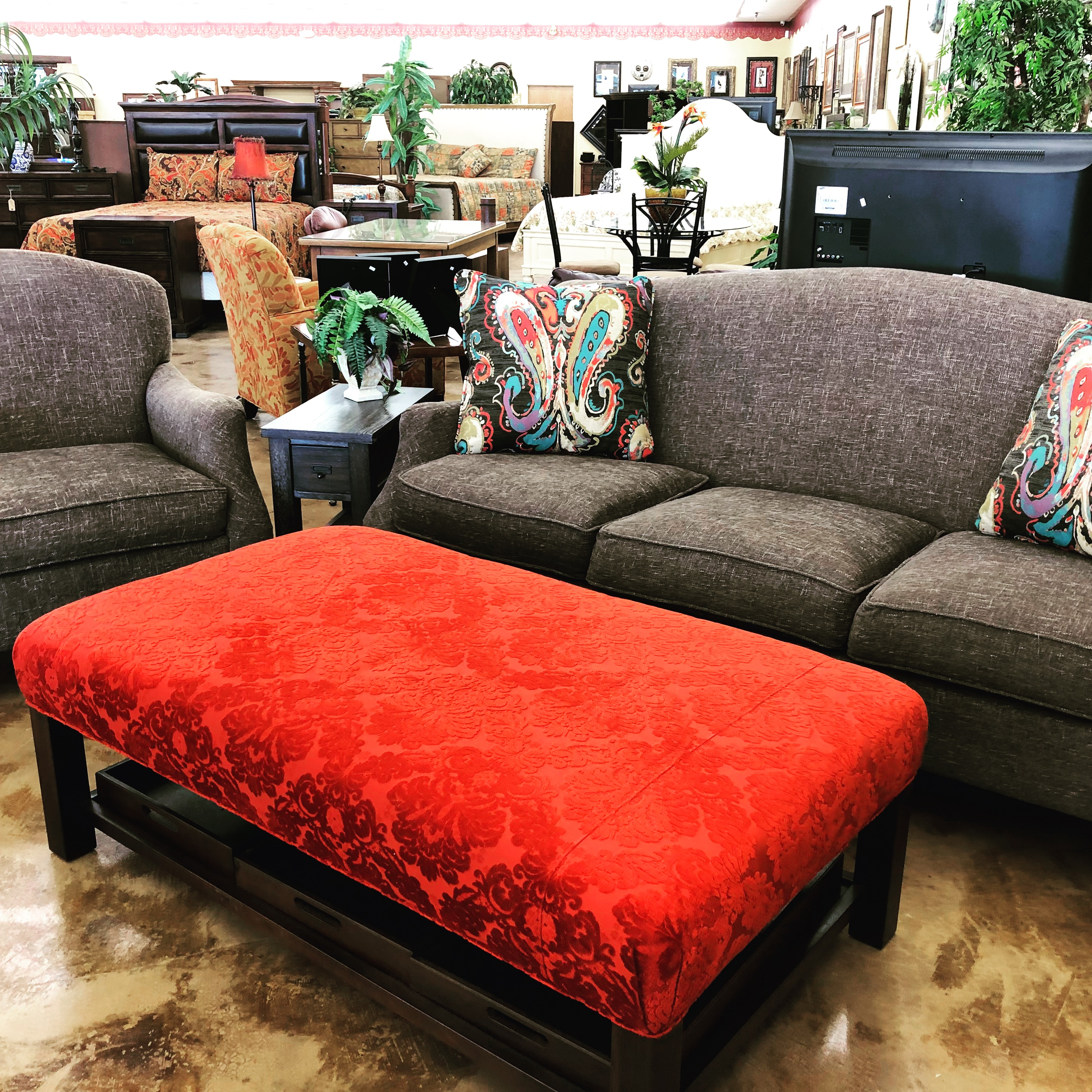 brown couch with red cushioned center table