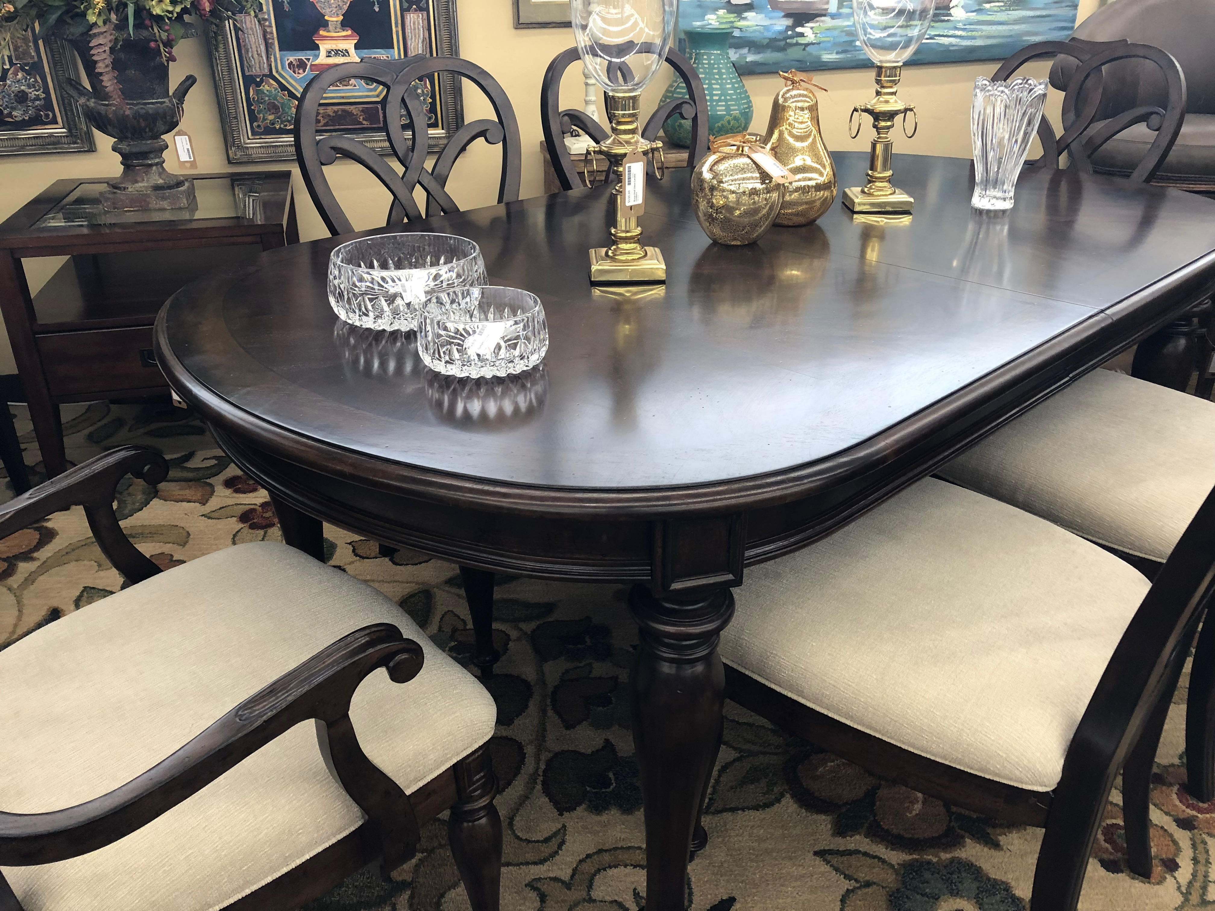 dark wooden dining table with white cushioned chairs