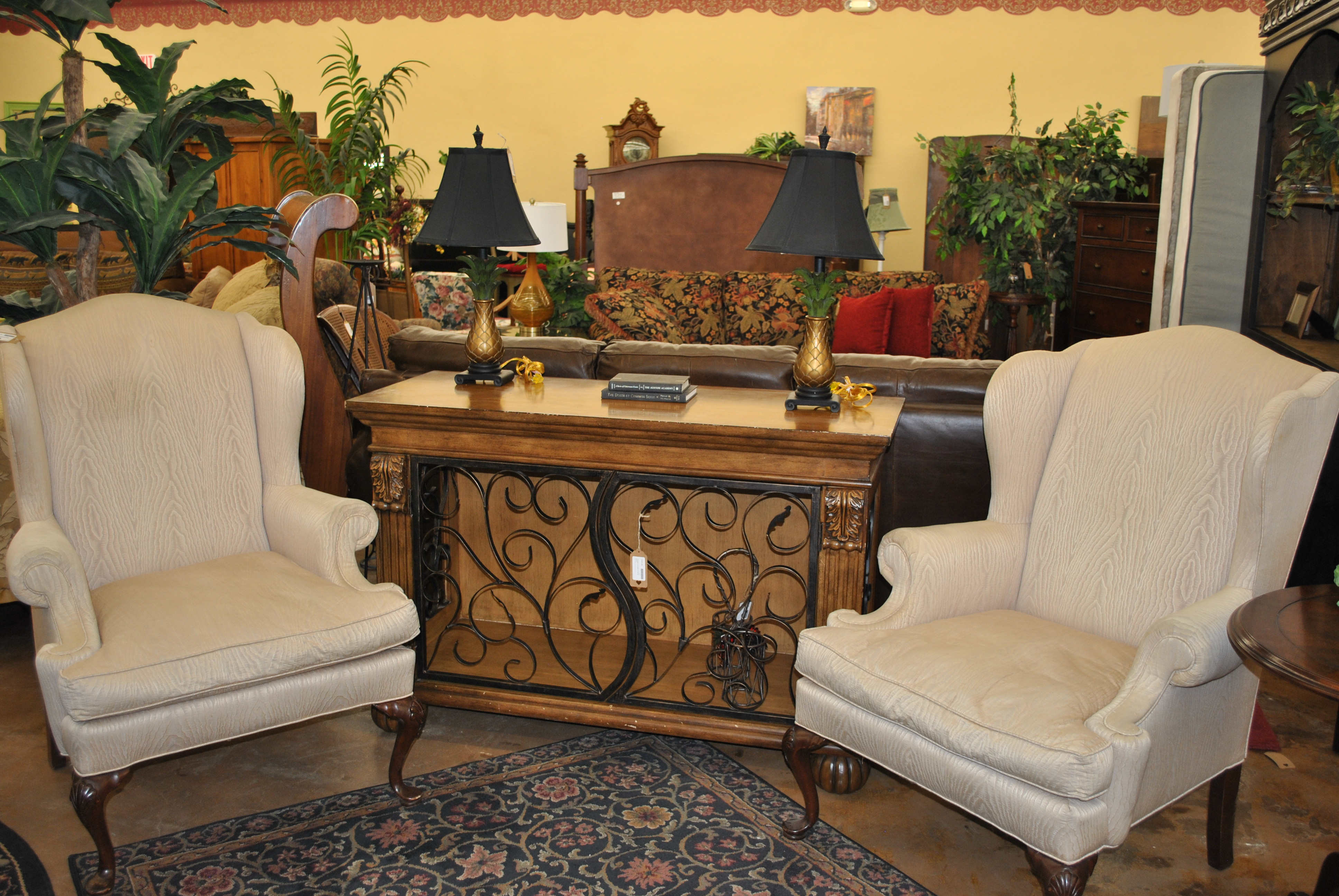 two plush beige chairs and light colored wooden cabinet