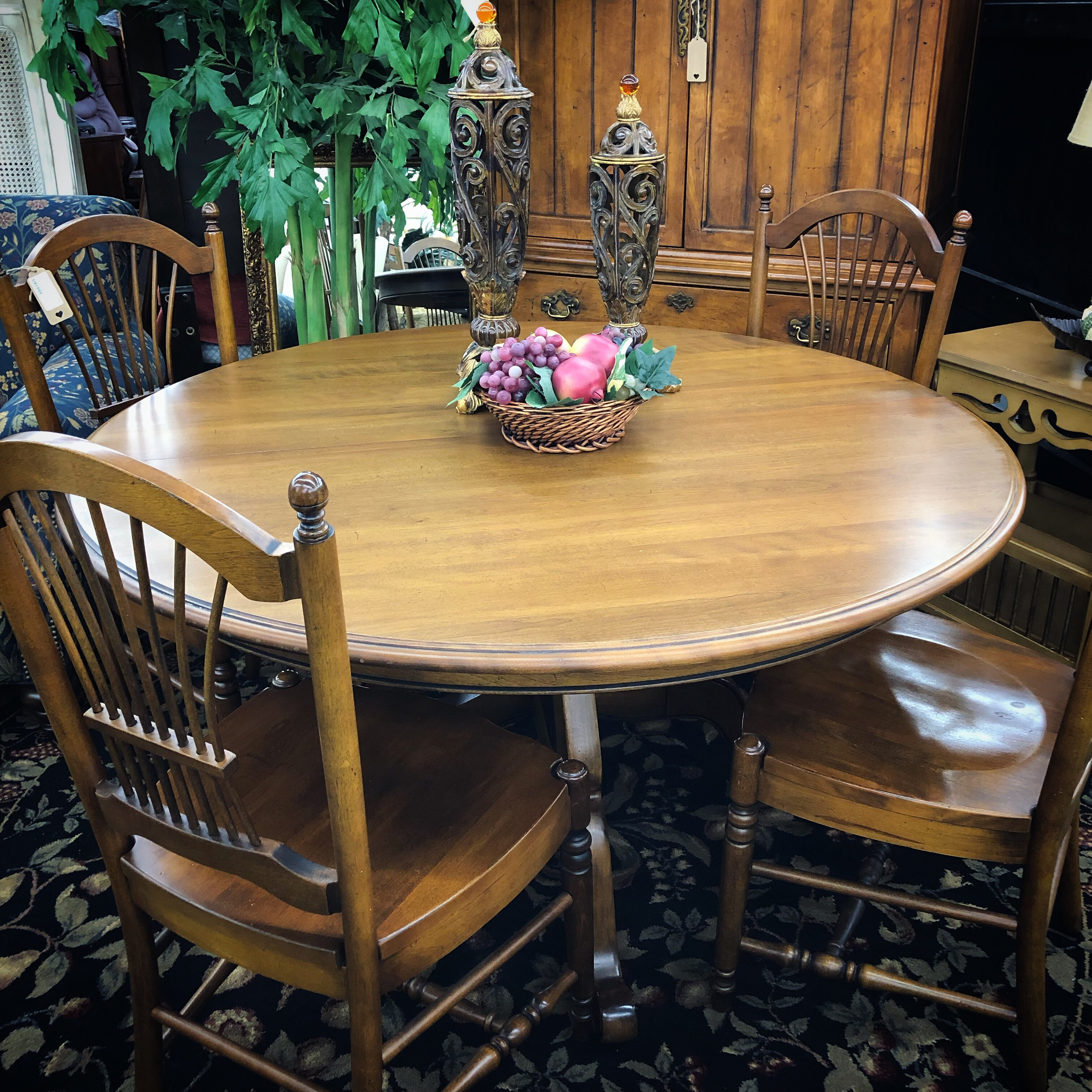 four chair round dining table made of maple colored wood